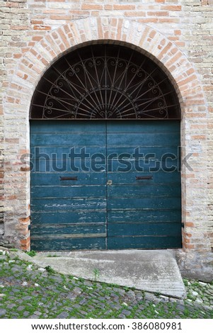 Old Italian architecture details. Blue wooden door with arch in old brick wall, background photo texture