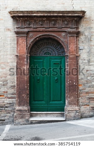 Old Italian architecture details. Green wooden door with arch and decoration in old brick wall, background photo texture - stock photo