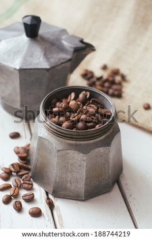 Old italian coffee maker with roasted beans - stock photo