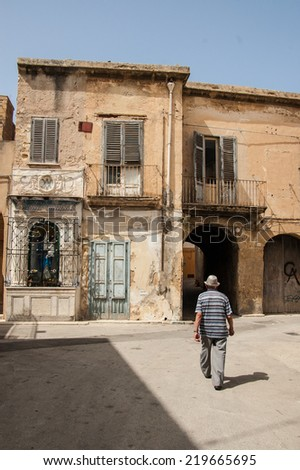 Old Italian man walking among decrepit houses in the medieval district  of Marsala, Sicily, Italy. - stock photo