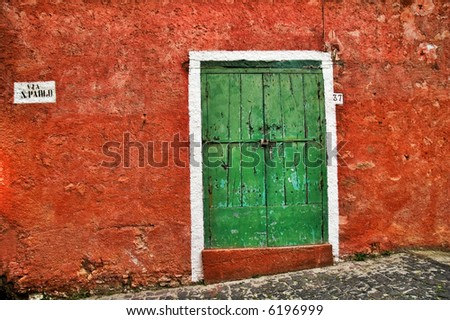 Old Italian red wall with green wooden door - stock photo