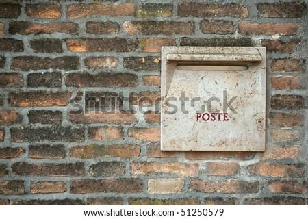 Old italian stone postbox in brick wall - stock photo