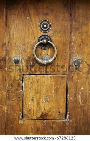 Old italian wooden door with metal knocker - stock photo