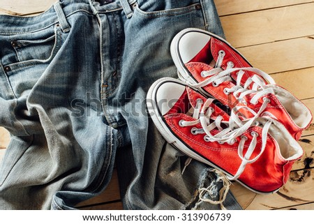 old jeans on wooden floor with a pair of sneakers,red sneakers and blue sneaker - stock photo