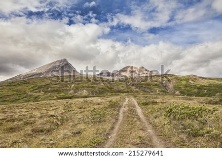 Old jeep trail in the mountains of the Yukon Territory in Canada in summer with puffy clouds. - stock photo
