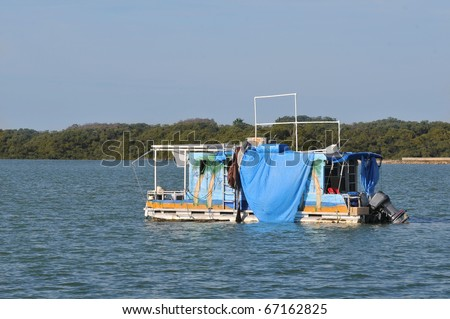 Old, jeri rigged, live aboard pontoon boat anchored in shallow water near park in Florida. Mural painted on the side - stock photo