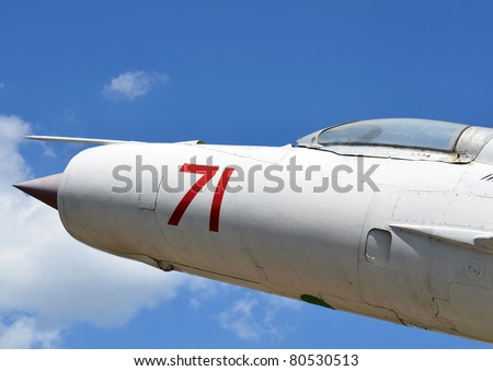Old jet fighter nose against blue sky - stock photo