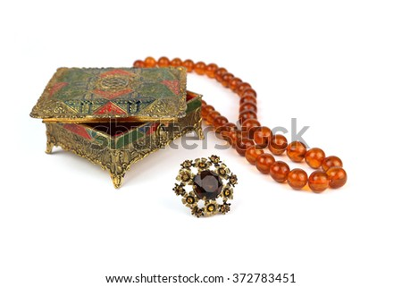 Old jewelry box, pearl amber necklace and vintage brooch on a white background - stock photo
