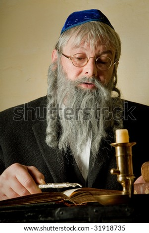 Old jewish man with beard reading with a torah pointer - stock photo
