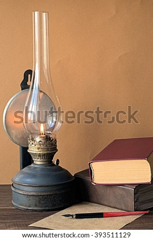 Old kerosene lamp, a pen with a feather and books on a brown background
