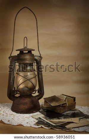 Old kerosene lamp and photos - stock photo