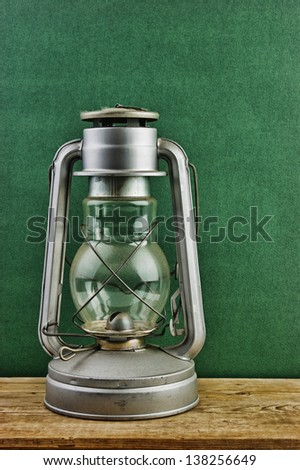 Old kerosene lamp on a wooden table against the wall