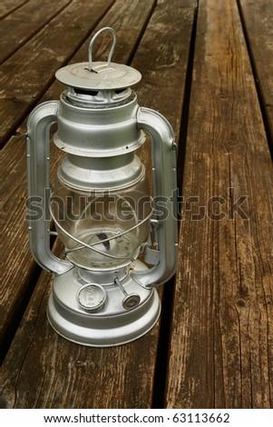 Old kerosene lamp on the old wooden table - stock photo