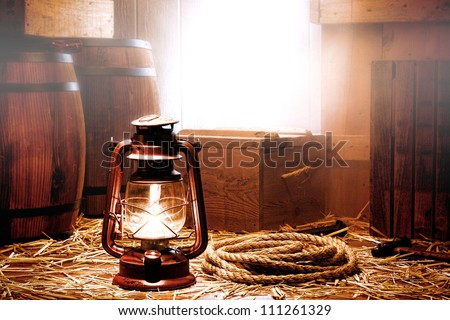 Old kerosene lantern lamp and aged rope with shipping crates containers and packaging boxes near transportation wood barrels in soft fog diffused light on an ancient port vintage wooden shipping dock - stock photo