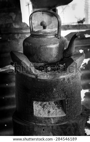 old kettle for boiling water on stove In kitchen the countryside ,Black and white tone - stock photo