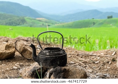 Old kettle on rock with blur rice field background.