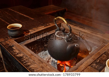 Old kettle put on a fireplace       - stock photo