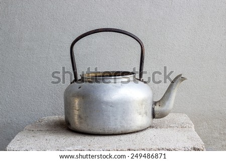 old kettle still life on brick block and concrete wall