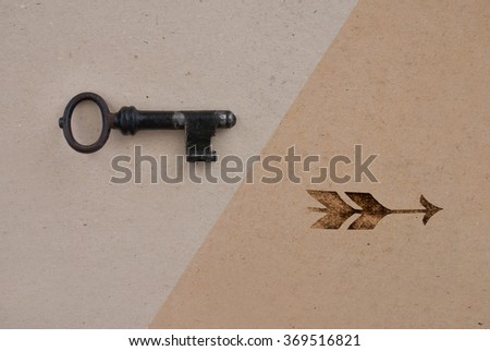 old key and arrow on golden ancient background - stock photo