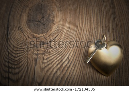 Old key and gold heart.Valentine's day greetings. - stock photo