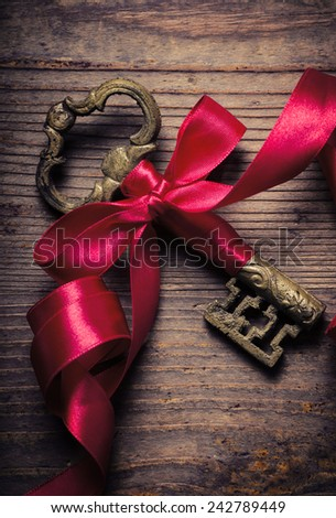Old key decorated with red ribbon  - stock photo