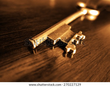 Old key laying on top of worn wood - stock photo