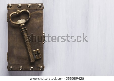 Old key on a locked box on a white wooden surface with space for text on the right side. - stock photo