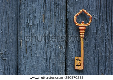 Old key on wooden antique door close-up - stock photo