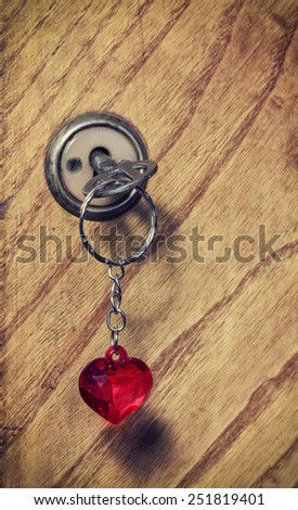 old key with a keychain heart, wooden background - stock photo