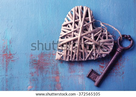 Old key with decorative heart on blue wooden background, close up - stock photo