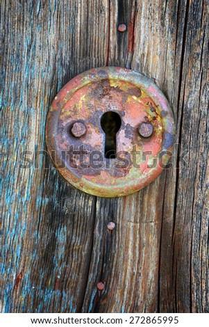 Old keyhole on aged wooden door - stock photo