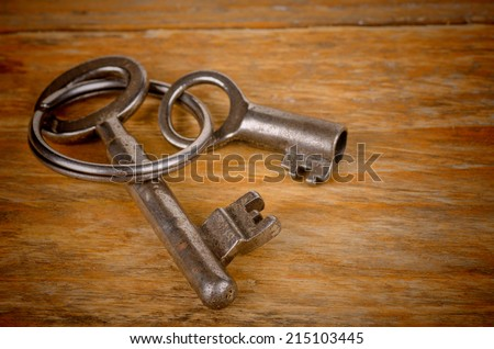 Old keys and key ring on a wooden background
