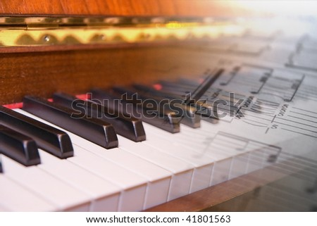 Old keys of piano and music score - stock photo
