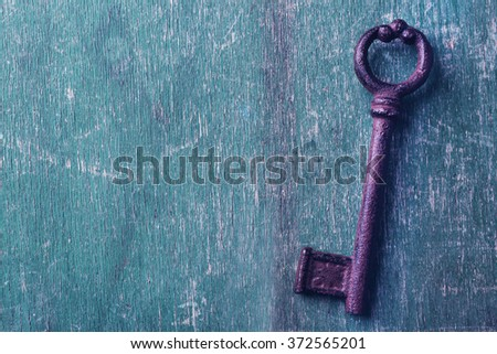 Old keys on green scratched wooden background, copy space - stock photo