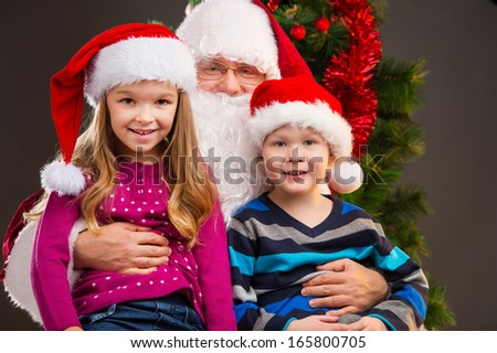 Old kind Santa Claus holding two little kids on his knees. Smiling and looking at camera with Christmas tree on background  - stock photo