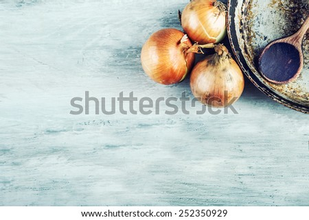 Old kitchen pan wooden spoon three onions on wooden table. Some of the equipment of the old kitchen in retro style  - stock photo