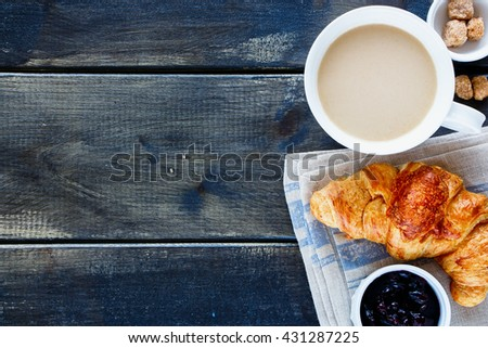Old kitchen table with breakfast set. Freshly baked croissant, blueberry jam and coffee on rustic wooden board over dark grunge backdrop, top view. - stock photo