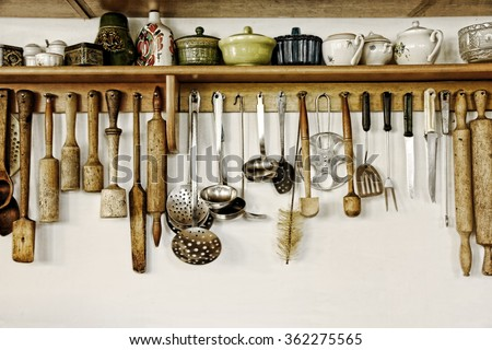 Old kitchen ware hanging on the white wall.Toned image. - stock photo