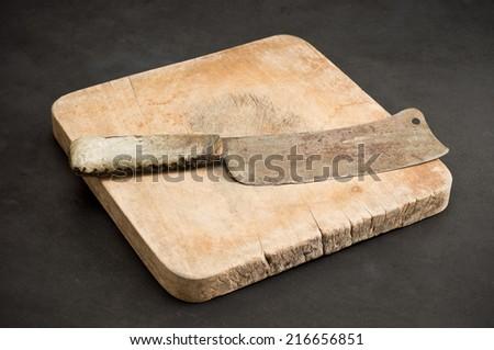 old knife with old chopping board on dark grunge background