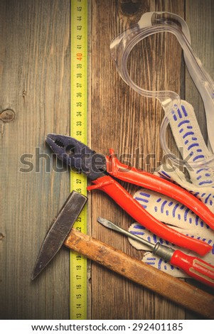 old knocker, ancient pliers, vintage screwdriver, safety gloves and glasses. instagram image filter retro style - stock photo