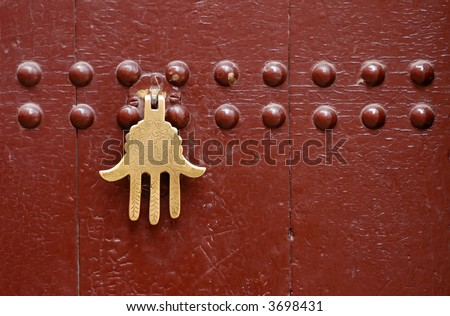 Old knocker in the shape of a hand on a door of a traditional Moroccan house in Marrakech, Morocco. - stock photo