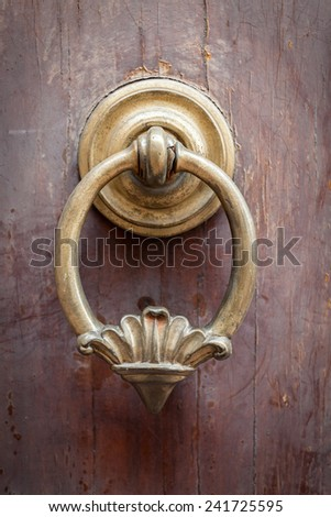 Old knocker on a wooden door located in Florence,Tuscany, Italy. - stock photo