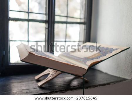 Old Koran book on window shelf - stock photo