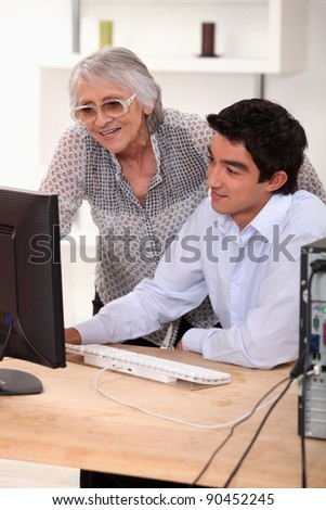 Old lady and young man sat by computer