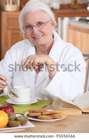 Old lady eating breakfast - stock photo
