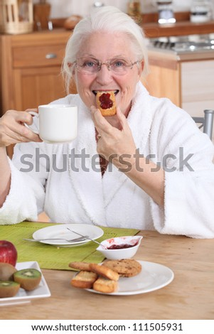 Old lady having breakfast in kitchen - stock photo