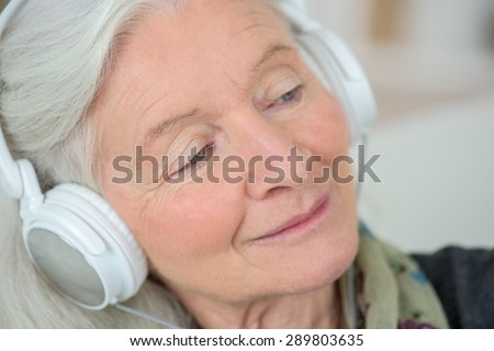 Old lady like to listen to music - stock photo
