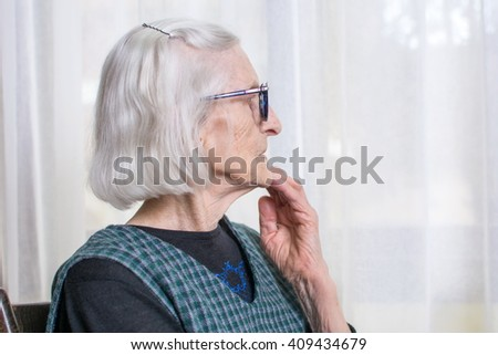 Old lady looking at her window to outdoors