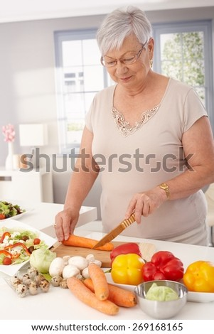 Old lady preparing healthy food from fresh vegetables in kitchen, slicing carrots. - stock photo