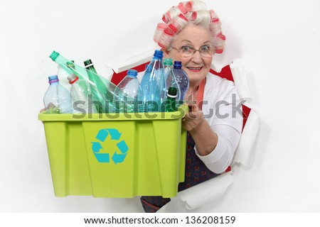 Old lady recycling plastic bottles - stock photo